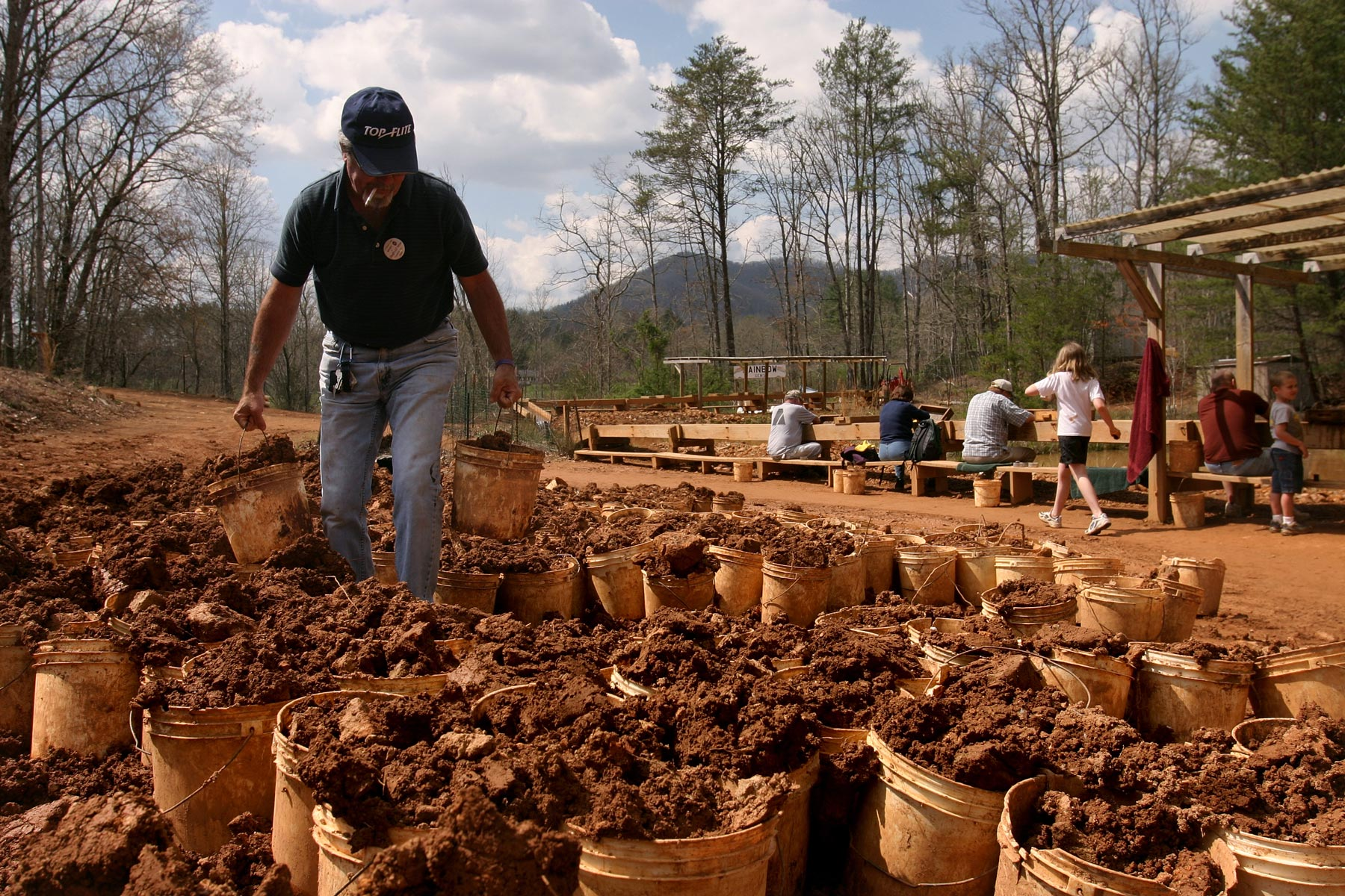 Man holding a bucket of dirt walks through a collection of similar buckets