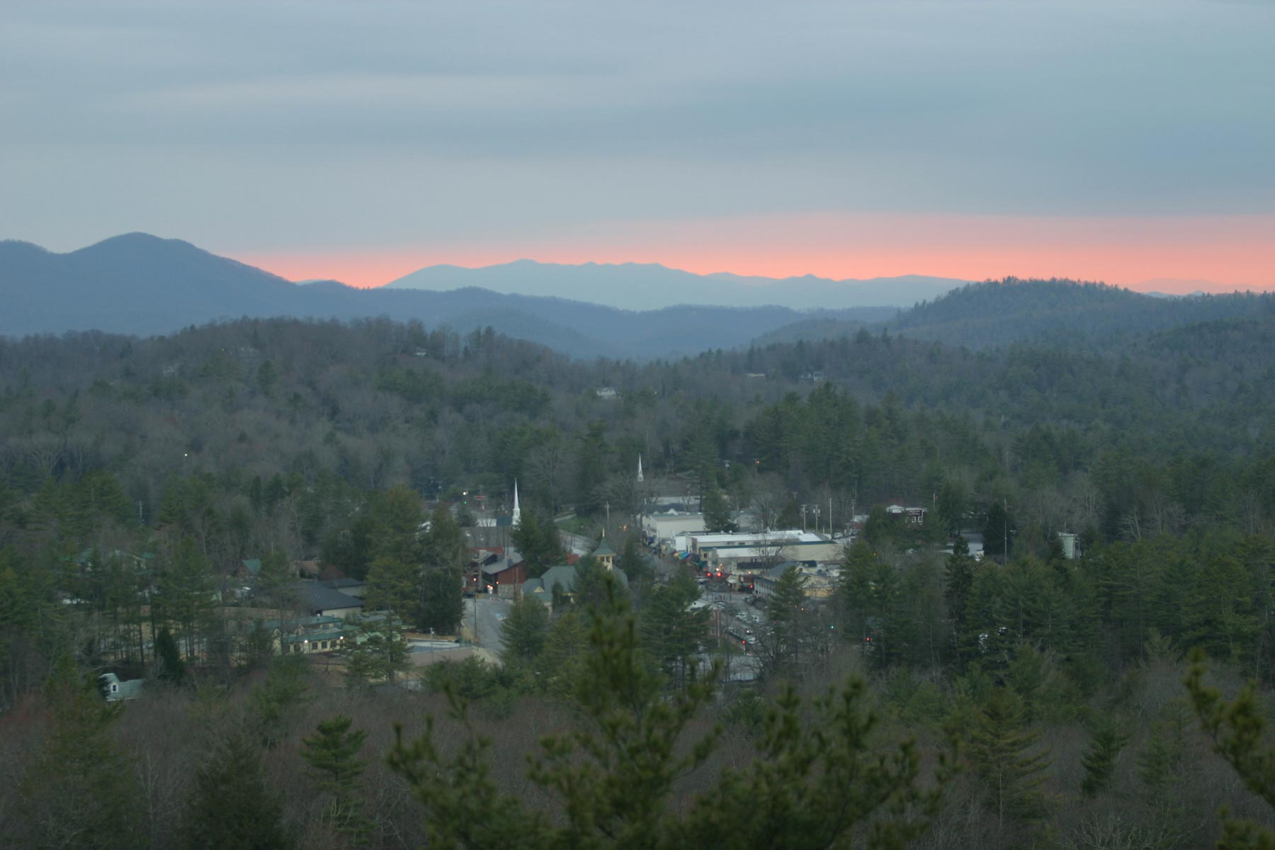 Sun sets over the green mountains of Highlands, NC