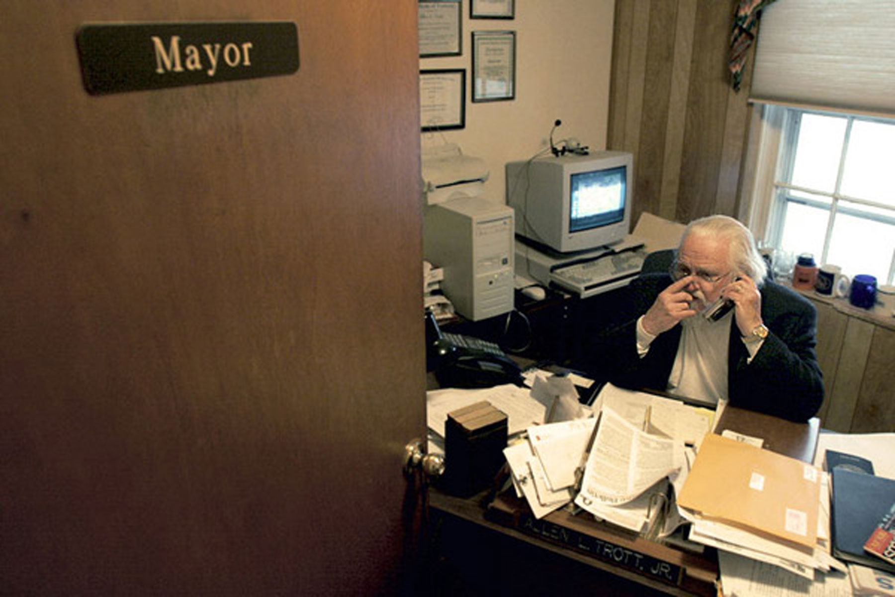 """Man sitting at desk piled with paperwork behind a door that says """"Mayor"""""""