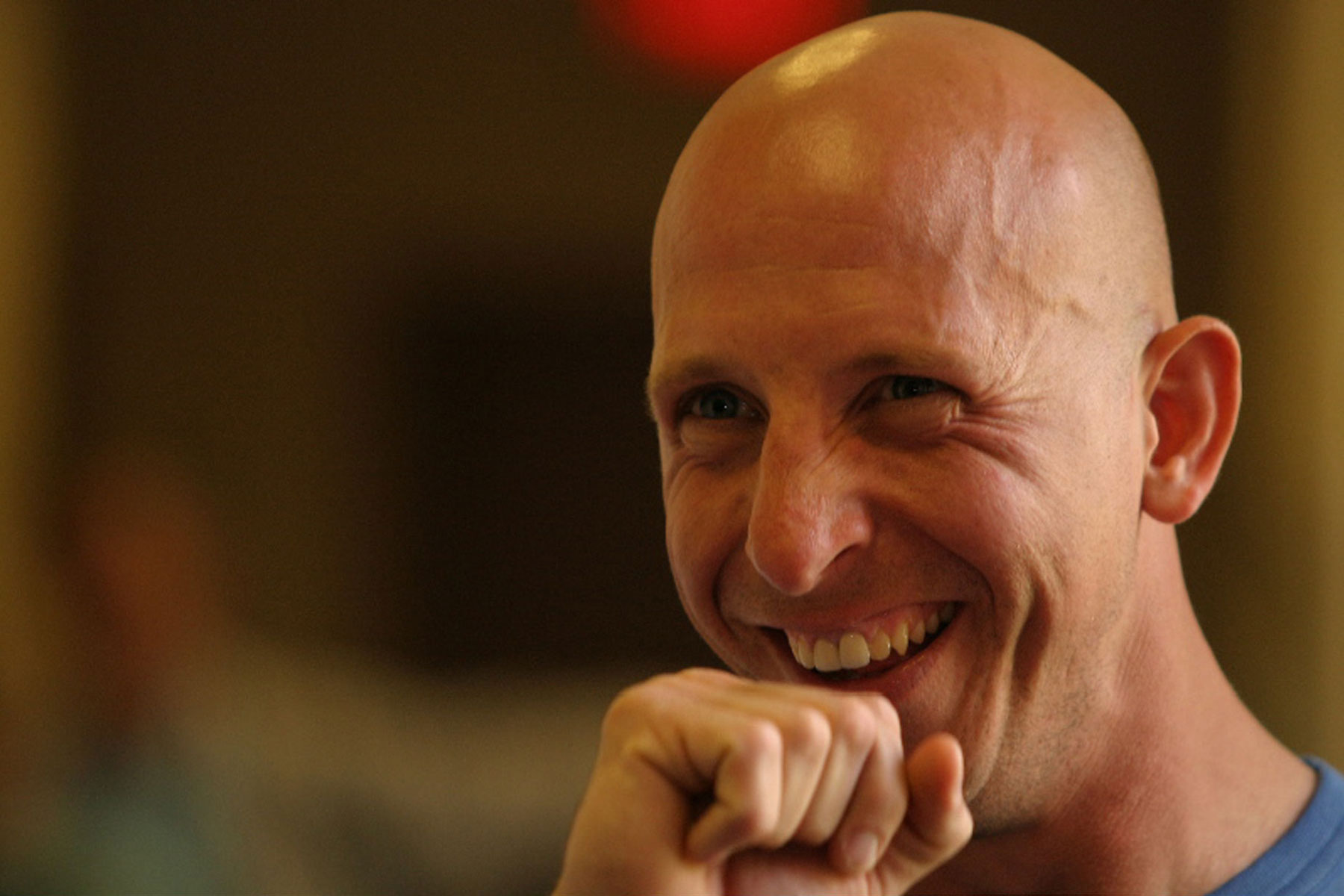 Bald man smiling with his fist held up to his chin