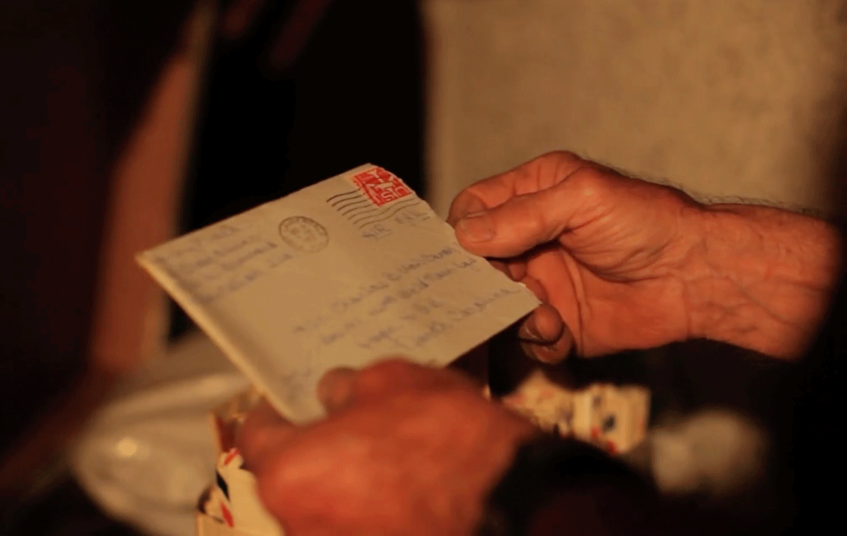 Hands holding an envelope with a letter inside
