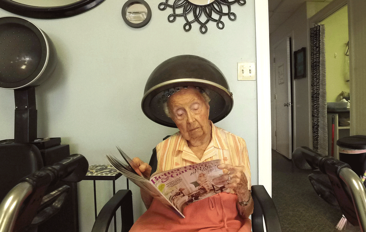 Woman reading a magazine while sitting in a beauty salon hair dryer